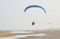 Paraglider in flight in blue sky over the beach Royalty Free Stock Images