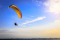 Paraglider flying in the blue sunny sky with clouds over the sea Royalty Free Stock Photo