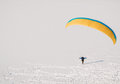 Paraglider lonely on a snowy lake in mountains Stock Image