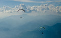 Paragliding two paragliders flying over the sky of italy Stock Images