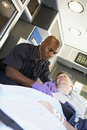Paramedic attending to patient in ambulance Stock Image