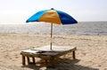 Parapluie de plage multicolore dans le support en bois sur la plage Images stock