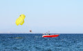 Parasailing over the sea behind a boat Royalty Free Stock Images