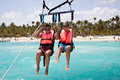 Parasailing together in summer happy couple dominicana beach couple under parachute hanging mid air having fun tropical paradise Stock Photo