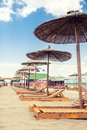 Parasol and deck chairs on a beach lounge sandy Stock Images