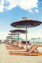 Parasol and deck chairs on a beach lounge sandy Royalty Free Stock Images