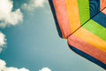 Parasol a multi colored in front of a blue cloudy sky Royalty Free Stock Images