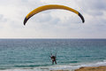 Paratrooper parachute landing on the beach near the mediteranian sea Stock Image