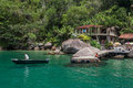 Paraty bay tropical beach large rocks a boat a marina the clear transparent green waters of a in and the forest rio de janeiro Stock Photography