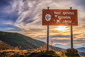 Parc natural de corse balagne corsica signpost riddled with hunter s bullet holes adainst a rising sun Royalty Free Stock Image
