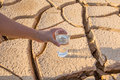 Parched soil and water i male hand holding a glass of over during drought dry season Stock Photo