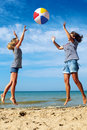 Parent and child play a ball at coast on a sunny summer day Royalty Free Stock Photo