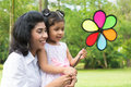 Parent and child playing windmill happy indian family outdoor activity candid portrait of at garden park Stock Photo