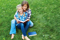 Parent and child reading books together in the park Royalty Free Stock Photo