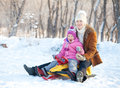 Parent with child walking in a winter park family parents on sled Royalty Free Stock Image