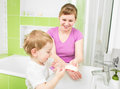 Parent and child washing hands with soap Stock Photo