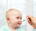 Parent feeding hungry baby home interior Royalty Free Stock Images