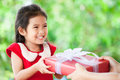 Parent giving Christmas gift to cute asian child girl Royalty Free Stock Photo