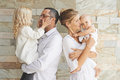 Parenthood concept happy father and mother holding daughters in their arms Stock Images