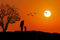 Parenting mother and baby silhouette walking down sunset storks flying from the tree towards sun family love bond unity Stock Photos