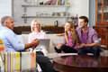Parents With Adult Offspring Using Digital Devices At Home Royalty Free Stock Photo