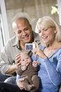 Parents with baby at home, mom holding camera Stock Photos