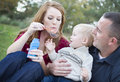 Parents Blowing Bubbles with their Child in Park Stock Photography