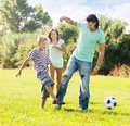 Parents with child playing with soccer ball happy at summer park Stock Images