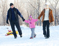 Parents with child walking in a winter park family on sled Royalty Free Stock Photo