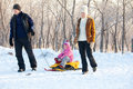 Parents with child walking in a winter park family on sled Royalty Free Stock Images