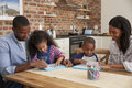 Parents And Children Drawing On Whiteboards At Table