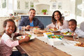 Parents and children eating at kitchen table look to camera Royalty Free Stock Photo