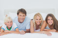 Parents and children lying on the bed looking at camera Stock Photo