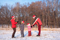 Parents and children in red hats play in winter
