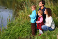 Parents with children sits on bank of pond