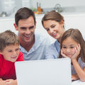 Parents and children using a laptop in the kitchen Stock Image
