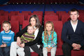 Parents with children watching a movie in the cinema Stock Photography