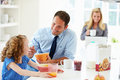 Parents and daughter having breakfast in kitchen together eating cereal smiling at each other Royalty Free Stock Photography