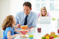 Parents and daughter having breakfast in kitchen together sitting at table eating cereal Stock Photography