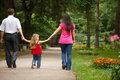 Parents with daughter walk on summer garden Royalty Free Stock Photos