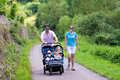 Parents with double stroller young active hiking in the mountains a twin two children brother and sister baby boy and toddler Royalty Free Stock Photos