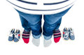Parents are expecting twins top view of father and mother feet and baby shoes wearing blue jeans and colorful socks Stock Images