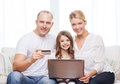 Parents and girl with laptop and credit card family child technology money home concept smiling little at home Royalty Free Stock Image