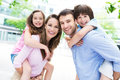 Parents giving kids piggyback ride portrait of a happy family outdoors Royalty Free Stock Photography