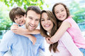 Parents giving kids piggyback ride portrait of a happy family outdoors Stock Image