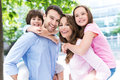 Parents giving kids piggyback ride portrait of a happy family outdoors Royalty Free Stock Image