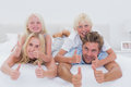 Parents giving piggy back to their children while giving thumbs up in bed Stock Photo