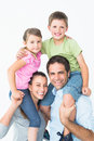 Parents giving their children piggyback ride smiling at camera on white background Stock Photos