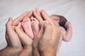 Parents hands holding feet of newborn lying over Royalty Free Stock Photo