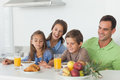 Parents having breakfast with children in the kitchen Stock Photos